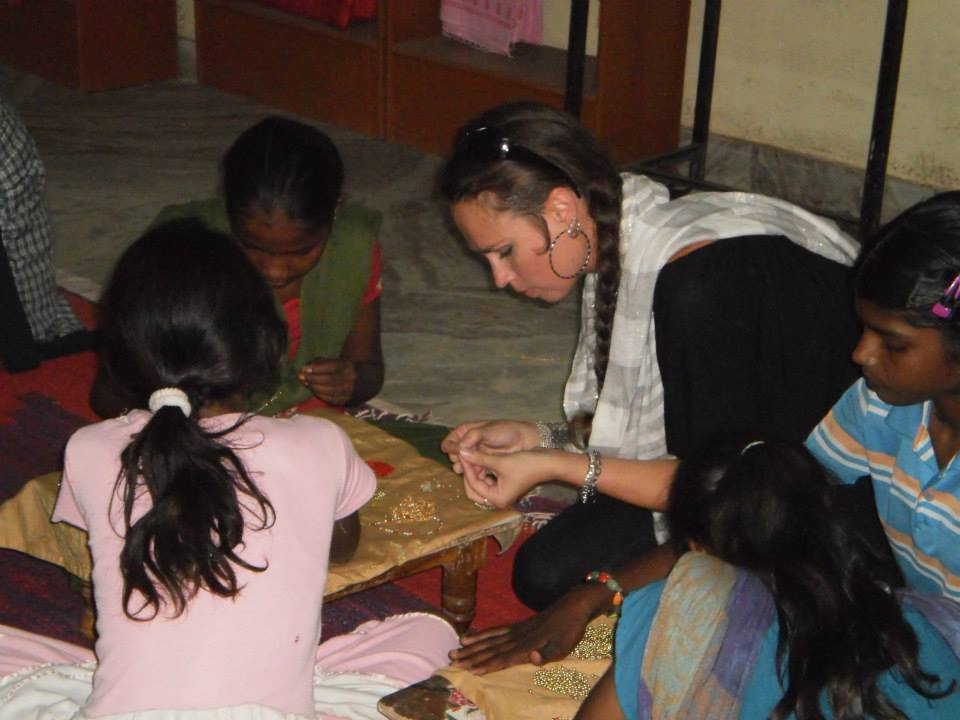 Dana joins the girls in making jewelry at Ladli